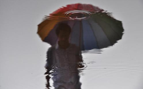 A reflection of a man in rain water walking at Ridge in Shimla on Thursday. Santosh Rawat-HT